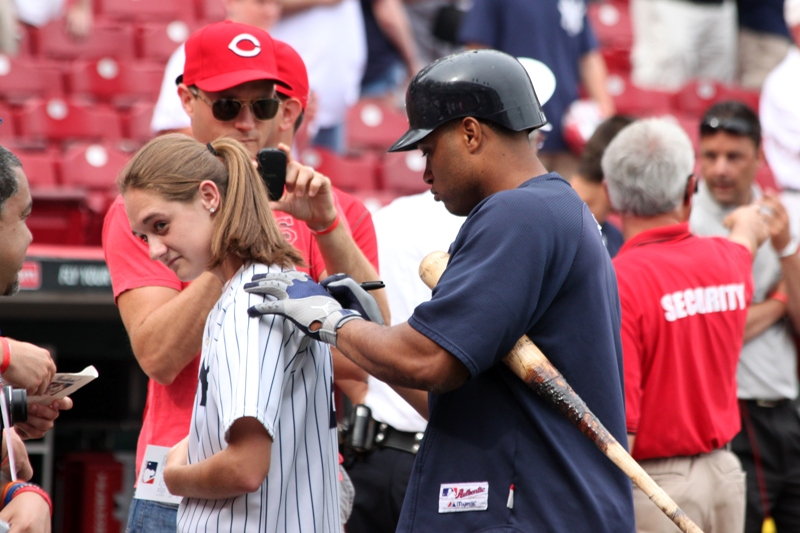 "Yankees second baseman Robinson Cano, scratches out ""Knoblauch"" on this young lady's jersey and replaces with his name"